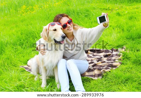 Owner woman with Golden Retriever dog taking selfie portrait on the smartphone in summer day - stock photo