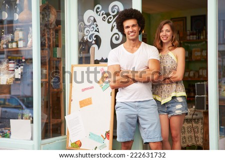 Owners Of Delicatessen Standing Outside Shop Together - stock photo