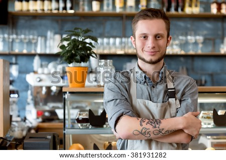 Owning coffee shop. Shot of a young barista posing near the showcase at his cafe - stock photo
