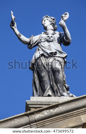 OXFORD, UK - AUGUST 12TH 2016: An old statue of an actor holding masks on top of the Clarendon Building in the historic city of Oxford, on 12th August 2016.