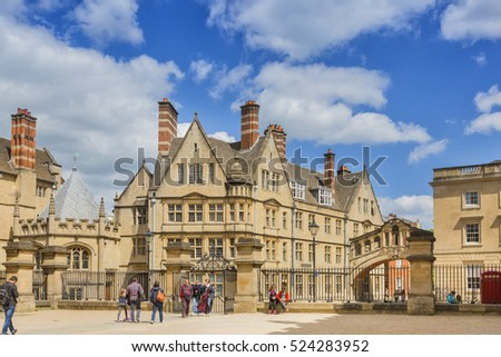 Oxford, UK - May 15, 2016; Entrance to the Bodleian library with Hertfor College opposite and its famous Bridge of Sighs. There are people walking