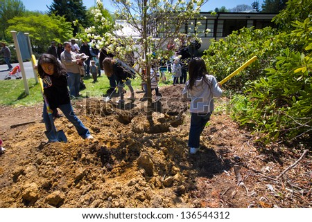 OYSTER BAY, NY - APR 29: Children assist in Tree Planting Ceremony at Arbor Day Celebration at Planting Fields Arboretum in Oyster Bay NY on April 29, 2012. The first Arbor Day was held in 1872 - stock photo