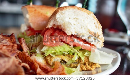 Oyster poor boy sandwich on a plate with chips - stock photo