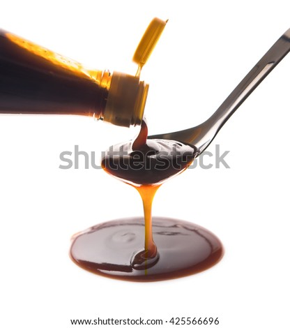 Oyster sauce poured from a bottle into a spoon on a white background - stock photo