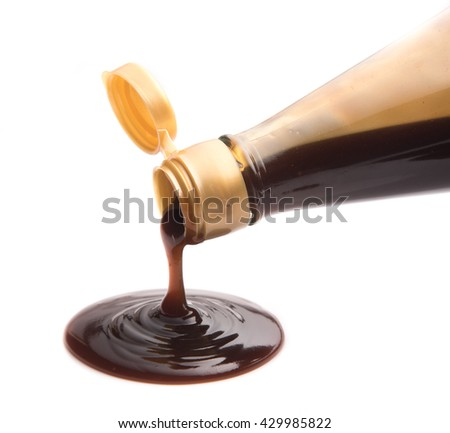 Oyster sauce poured from a bottle on a white background - stock photo