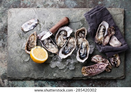 Oysters on stone plate with ice and lemon - stock photo