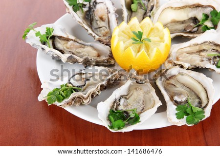 Oysters on wooden background - stock photo