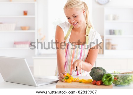 p of a blonde woman using a notebook slicing a pepper in her kitchen