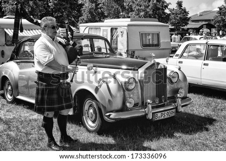 PAAREN IM GLIEN, GERMANY - MAY 19: Piper plays the Great Highland Bagpipe near the car Rolls-Royce Silver Cloud, black and white, The oldtimer show in MAFZ, May 19, 2013 in Paaren im Glien, Germany - stock photo