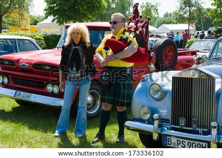 PAAREN IM GLIEN, GERMANY - MAY 19: Piper plays the Great Highland Bagpipe near the car Rolls-Royce Silver Cloud, The oldtimer show in MAFZ, May 19, 2013 in Paaren im Glien, Germany - stock photo