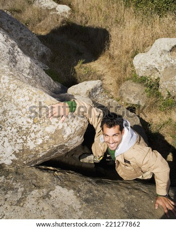 Pacific Islander man climbing rock formation - stock photo