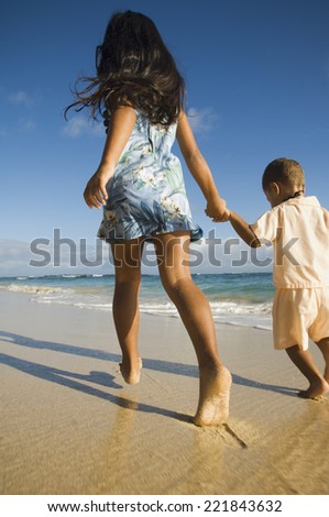 Pacific Islander sister and brother walking on beach - stock photo