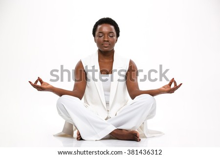 Pacified pretty african american young woman sitting and  meditating in lotus pose over white background - stock photo