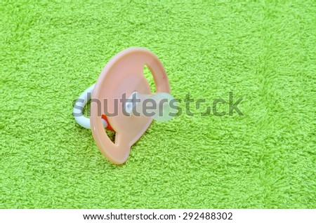 Pacifier on the green towel - stock photo