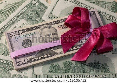 Pack of dollar bills with red bow - stock photo