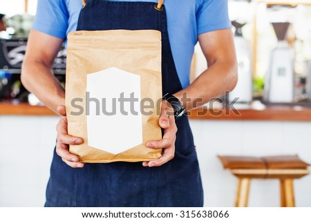Package design template mockup. Man holding blank coffee package