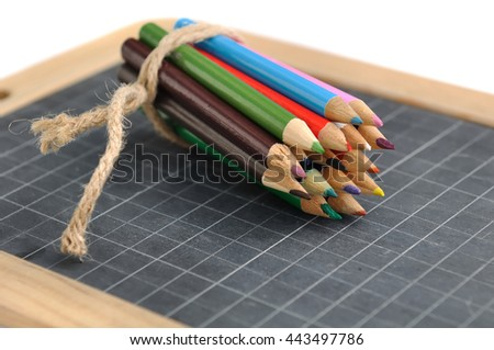 package of colored pencils on a slate on white background - stock photo