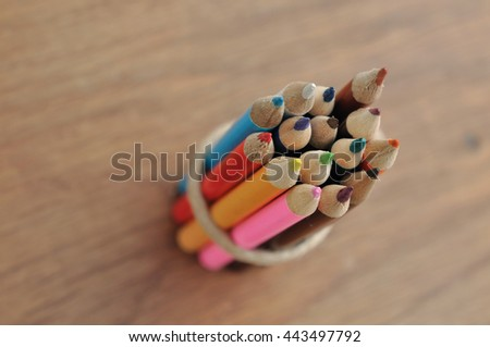 package of colored pencils on wooden background - stock photo