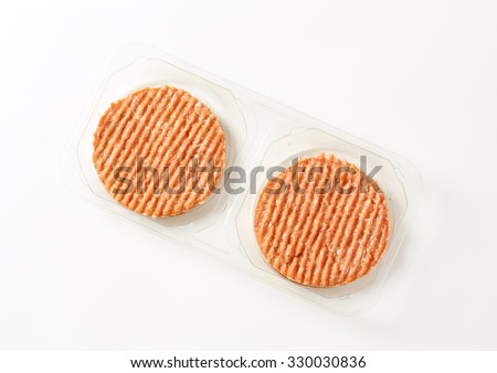 package of raw burger patties on white background - stock photo