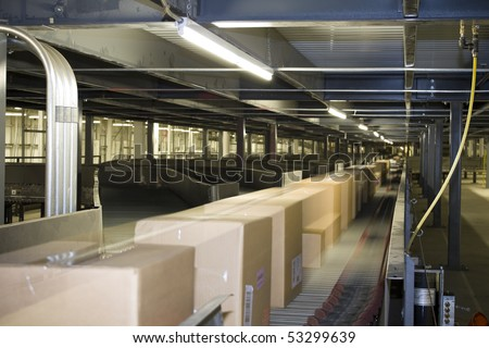 Packages distributed on conveyor belt on automated system - stock photo