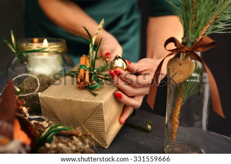 Packaging holiday gifts.Woman packs a Christmas gift and decorating the house with Christmas decorations  - stock photo