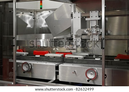 Packaging machine for packing ketchup in plastic bottles - stock photo