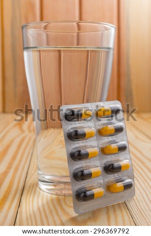 packaging of pills and capsules of medicines and a glass of water placed on a wooden table, warm tone photo. - stock photo