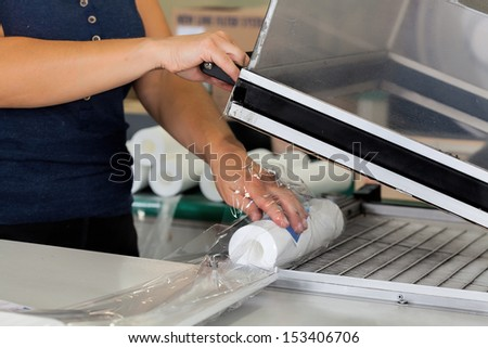 Packaging products in a factory, closeup of a worker hands - stock photo