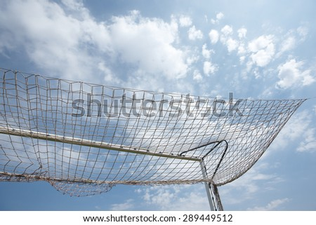 Packed football goal net and blue sky. Horizontal
