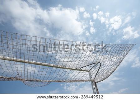 Packed football goal net and blue sky. Horizontal - stock photo