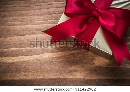 Packed glittery gold present container on vintage wooden board. - stock photo
