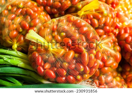 Packed in bags for sale fresh organic tomatoes. Vegetables at food market - stock photo