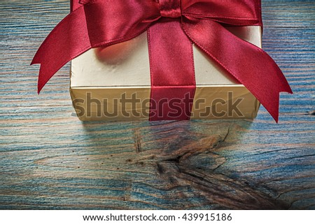 Packed present box on vintage wooden board directly above holidays concept. - stock photo