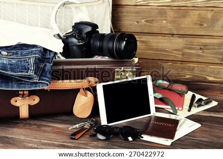 Packed suitcase of vacation items on wooden background - stock photo