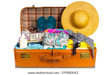 Packed vintage suitcase full of vacation items. - stock photo