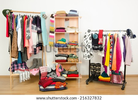 Packing the suitcase for winter vacation. Wardrobe with clothes nicely arranged and a full luggage. Dressing closet with colorful winter clothes and accessories on hangers and a shelf. - stock photo