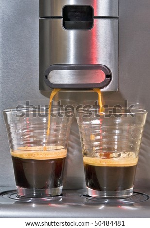 Pad coffee maker brewing two cups of hot coffee