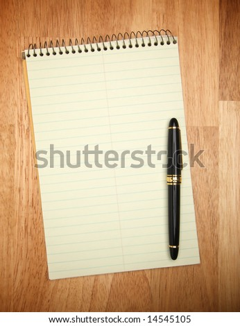 Pad of Paper & Pen on a wood background. - stock photo