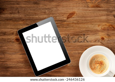 Pad pc and cup of coffee on wooden desk - stock photo