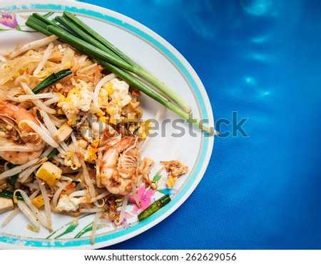 Pad thai is favorite part of Thailand's cuisine. Pad thai is fried noodles with shrimps, tofu, soy sprouts and eggs. Usually pad thai is serviced with green onion and lime. - stock photo