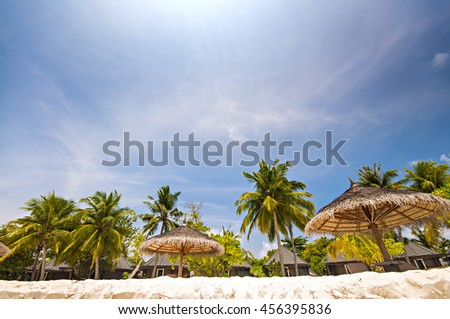 Padaraise tourist beach with white sand, palm trees and sun loungers - stock photo