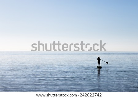 Paddle-boarding on open water. - stock photo