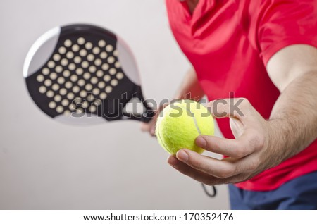 Paddle tennis player ready for serve on gray background