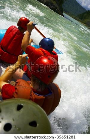 paddling team on a raft and splashing water - stock photo