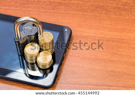 Padlock and gold coins on a Tablet PC. Data security concept