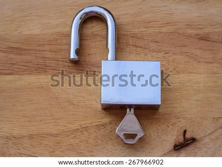 padlock key on wood background - stock photo