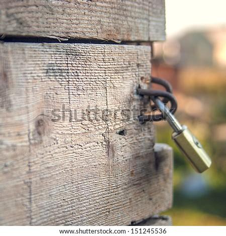 Padlock on a old wooden door - stock photo