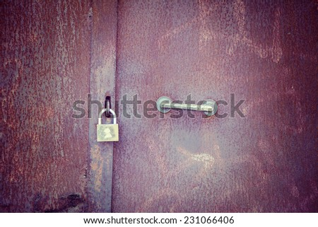 Padlock on a rusty metal door. Processed for vintage tone effect. - stock photo