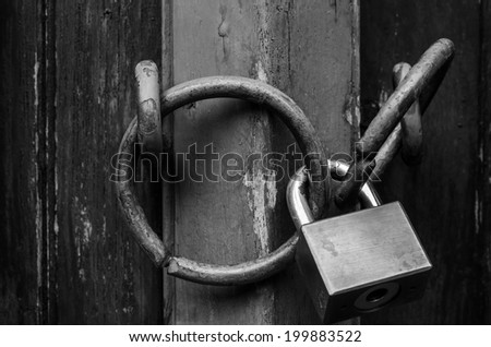 Padlock on ancient style wooden door, close up. - stock photo