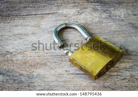 padlock saw-off on wood background - stock photo